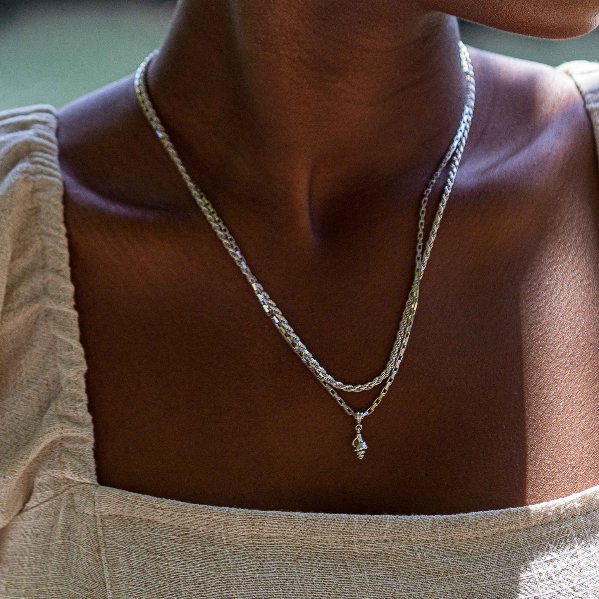 Whelk Shell Necklace Charm in Silver worn on a rectangular link chain