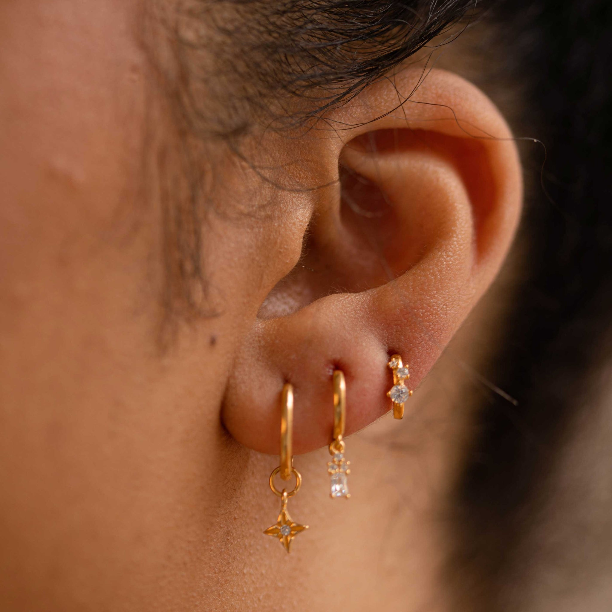 Triple Stone Huggies in Gold worn with gold earrings