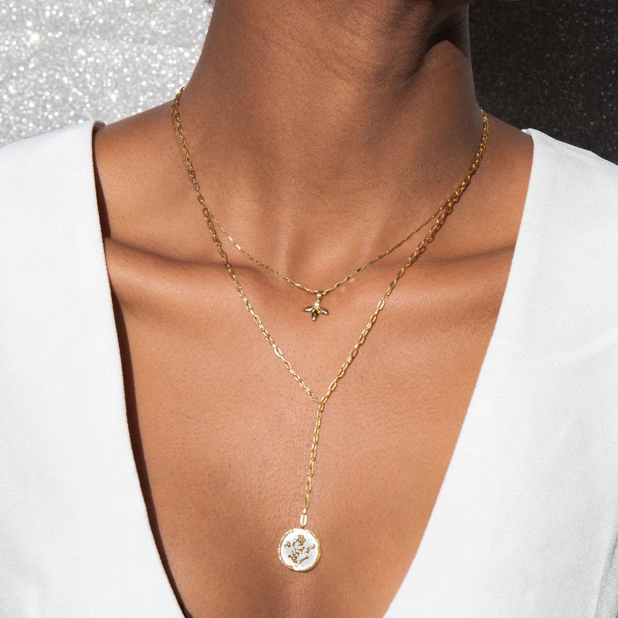 gold dainty pendant necklace worn with gold lariat necklace