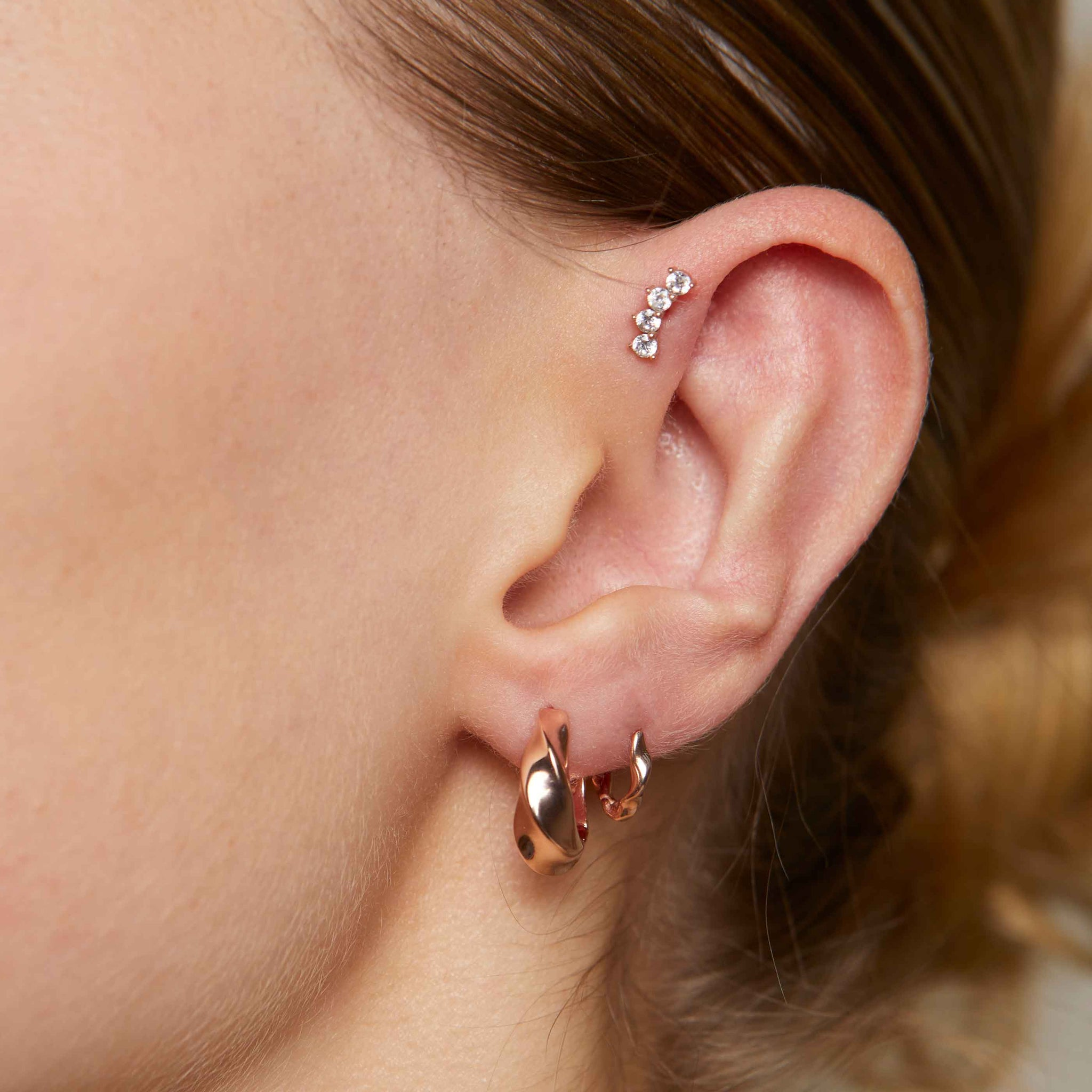 Elemental Huggies in Rose Gold worn with elemental hoops