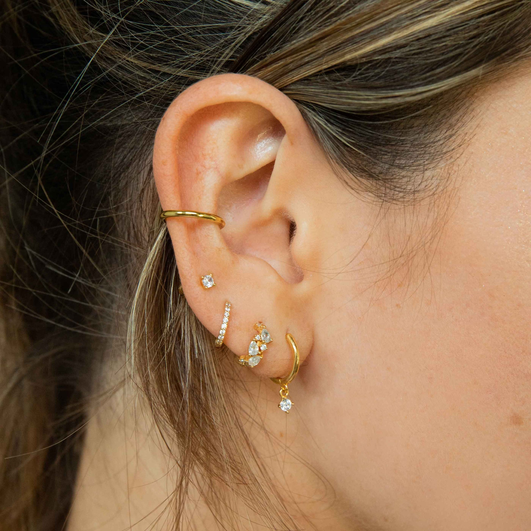 mystic crystal huggies in gold worn with hoops