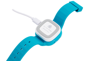 A charging kit with a USB cable inserted on the side, is plugged into a Spacetalk Kids watch