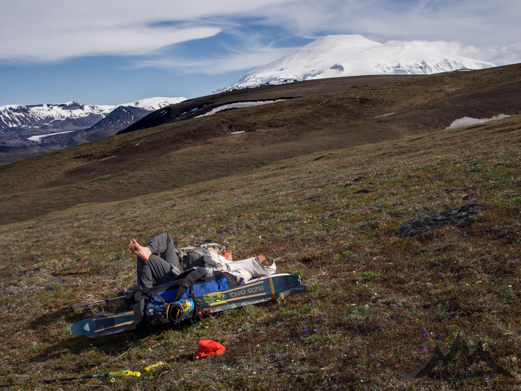 It's supposed to get easier as you exit big expedition peaks. Not so with our chosen tactics on Mount Sanford… Even when the walking was smooth, as it can be on the tundra, our packs were huge! Meagan lounges as Mount Sanford just doesn't seem to shrink behind us. Photo by Jed Porter.