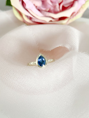 White gold and blue pear shaped sapphire and diamond ring
