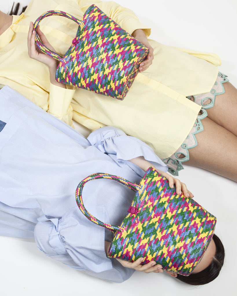 models laying on the floor with multicolour straw basket bags