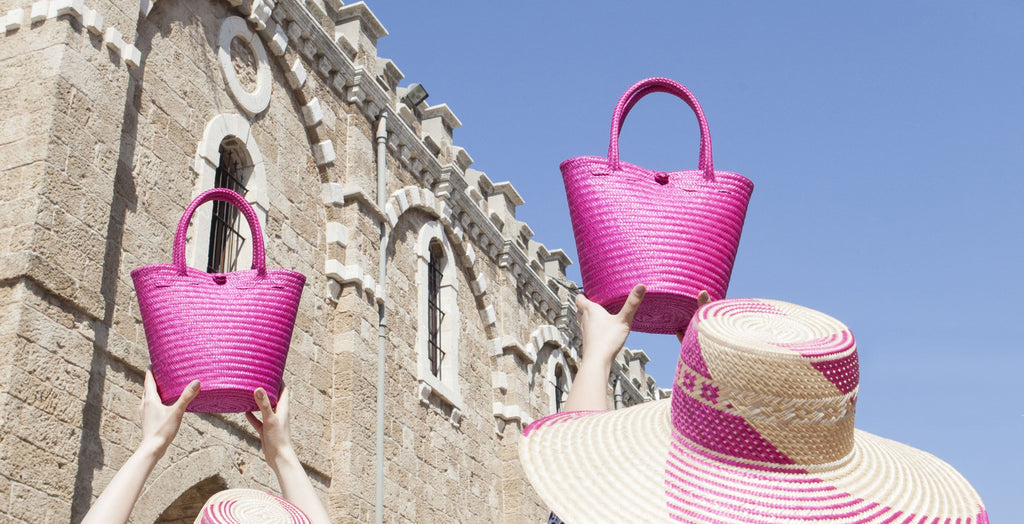 two fuchsia straw bags lifted up with a church and blue sky in the background