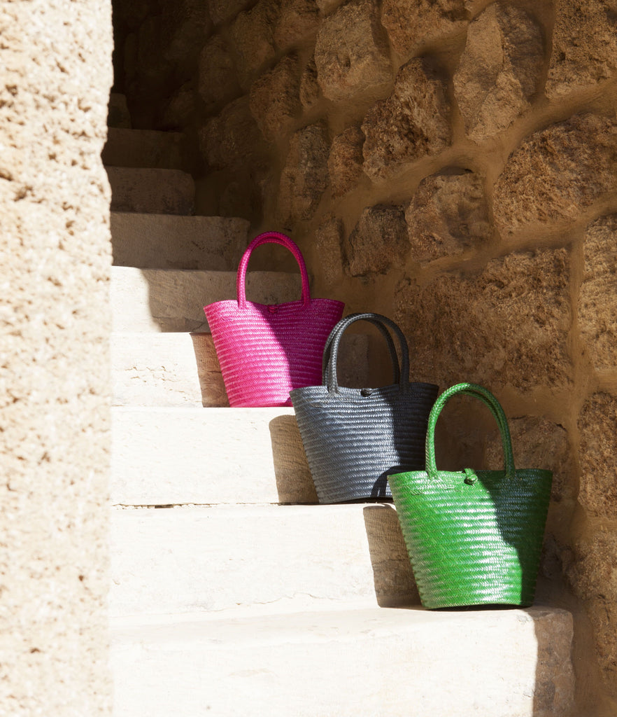 three straw bags in green blue and fuchsia