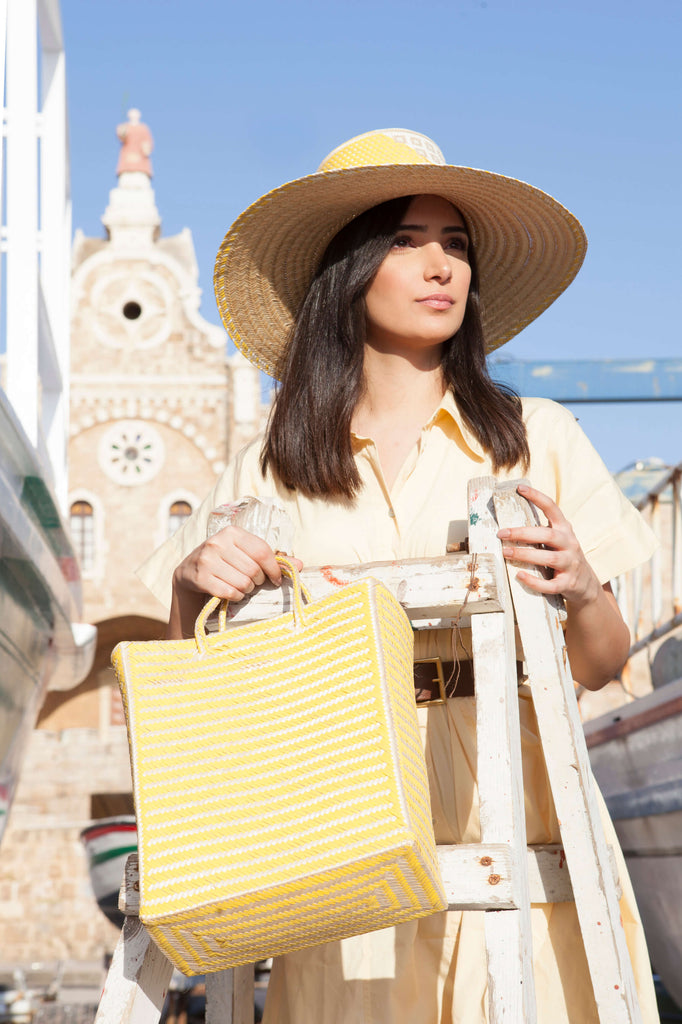 model looking to the horizon with a yellow straw hat and bag