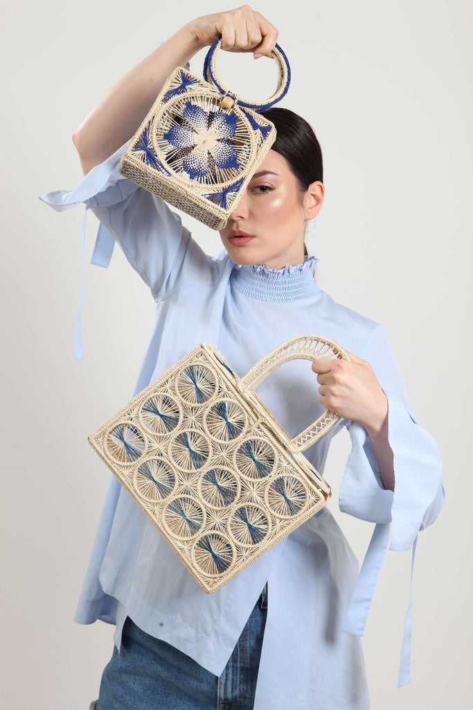 model holding two iraca bags