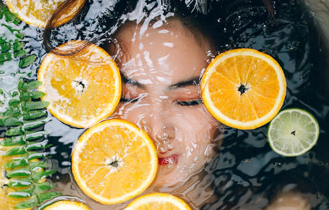 Woman underwater with citrus floating.