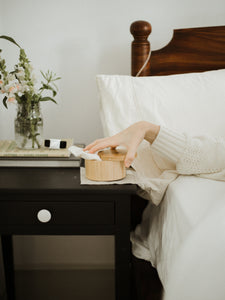Woman reaching for body stone bamboo canister on bed-side table