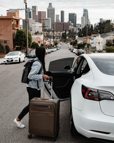 Woman entering car with luggage