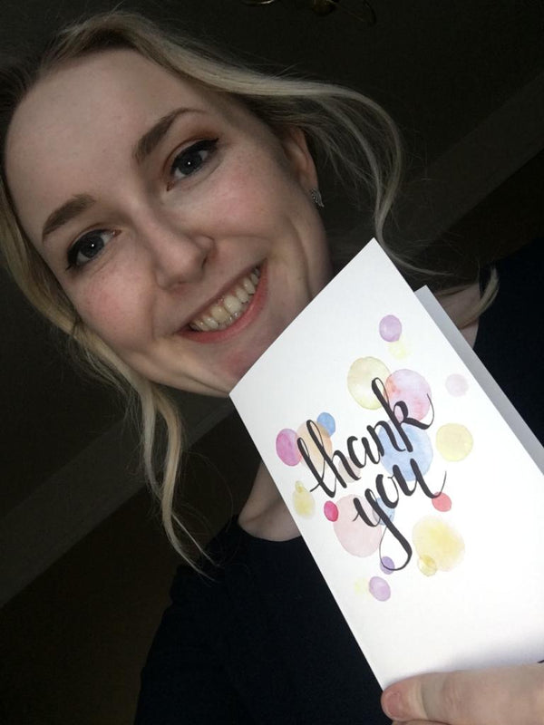 Rachel holding a thank you card from Into University