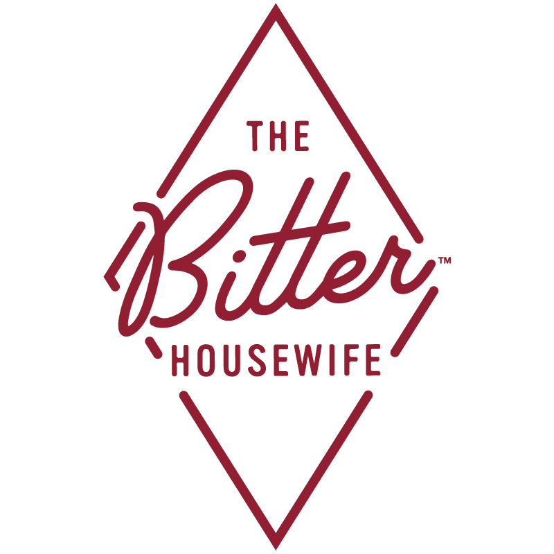"A red diamond with text inside that says ""The Bitter Houswife"""