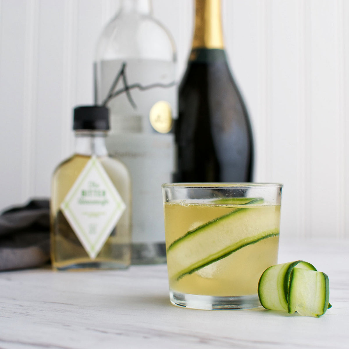 A cocktail with cucumber peels in a clear glass and a bottle of Lime and Coriander Bitters in the background