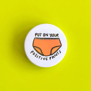 "White 38mm badge with writing ""put on your positive pants"" with orange pants in the middle."