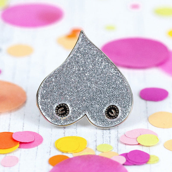 Enamel pin badge in the shape of a pair of boobs in silver glitter with silver nipples