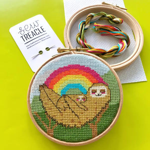 Completed cross stitch kit featuring a sloth holding a sloth baby with a rainbow background.