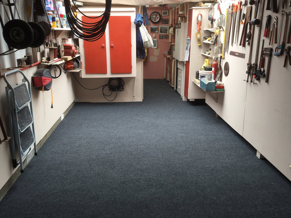 Garage with lots of tools on the wall with charcoal garage carpet laid