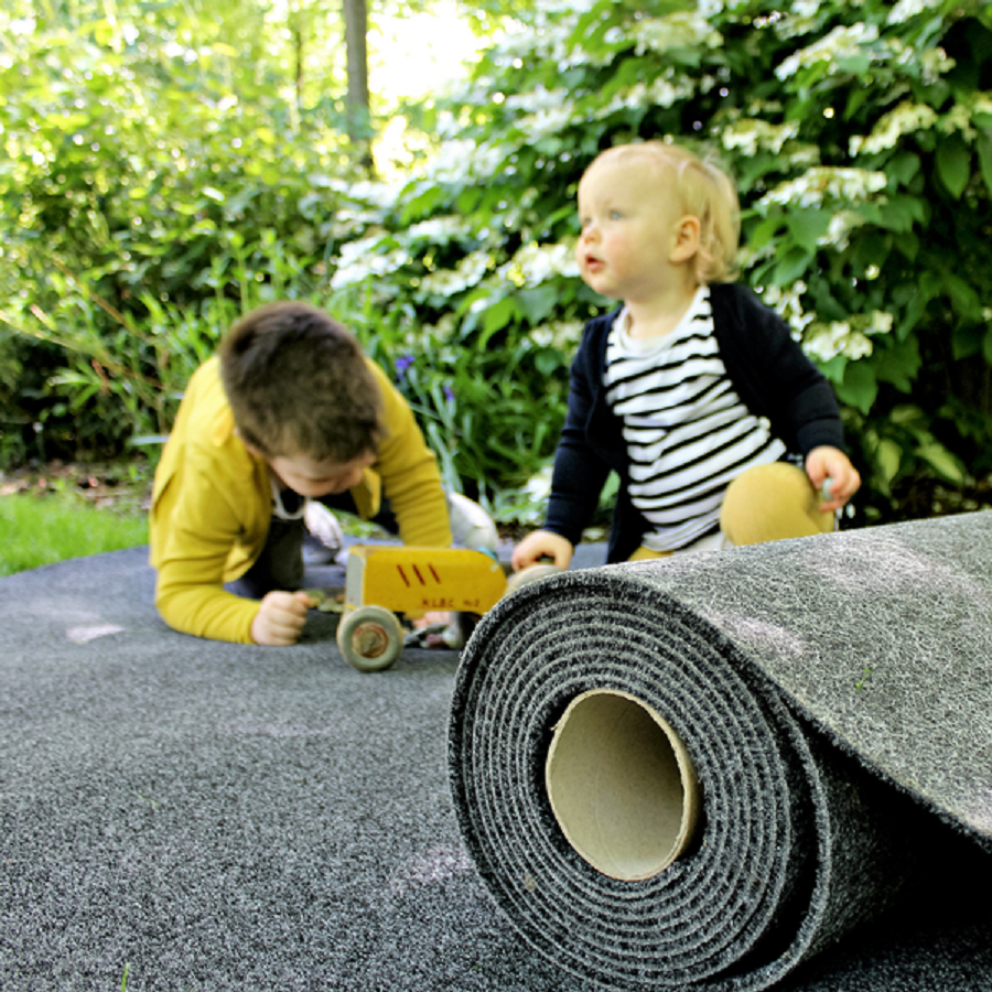 2 kids plying with a toy tractor on a garage carpet roll