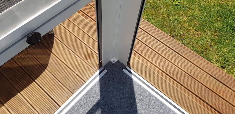 Outdoor patio with light grey carpet laid with aluminium edging surrounding it