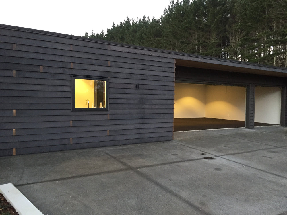 Timber house in Auckland with garage open showing freshly installed garage carpet with pine trees in the background