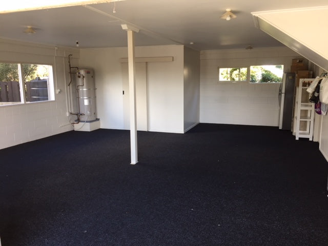 garage with a pole in the centre with newly installed charcoal garage carpet