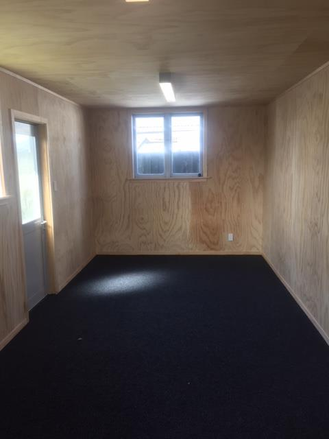 garage with plywood walls with garage carpet on the floor