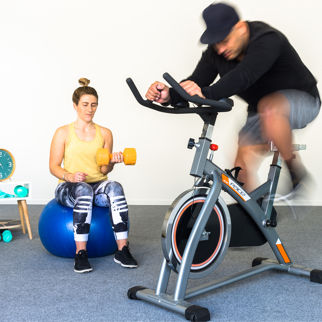Man working out on a exercise bike on top of garage carpet and a lady on a Swiss ball with a dumb bell in her hand working out