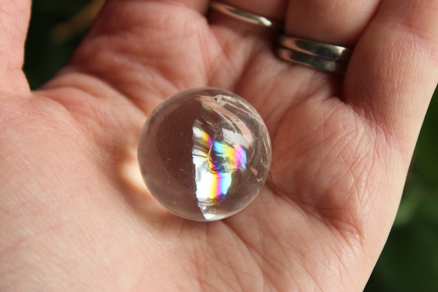 Clear quartz sphere with rainbow inclusions 1