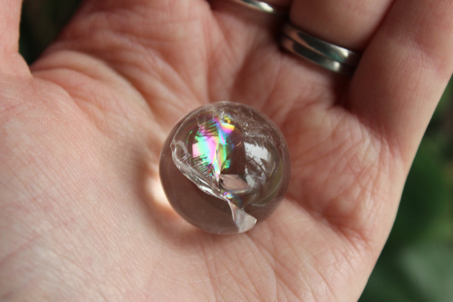 Clear quartz sphere with rainbow inclusions 20