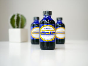 Image of 3 bottles of Dr. Singha's Mustard Rub on a white table with a small cactus in the background