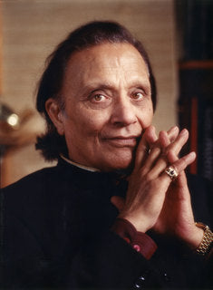 Image of Dr. Singha sitting, wearing a black outfit with his fingers intertwined