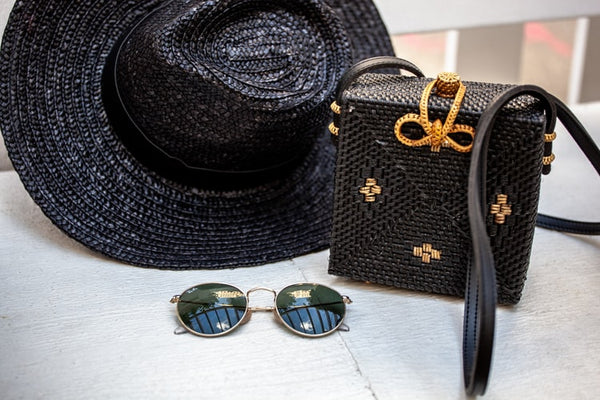 black-mini-bag-next-to-sunglasses-and-sun-hat-on-a-table-jpeg