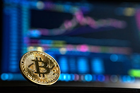 physical-bitcoin-with-trading-website-in-the-background-jpg