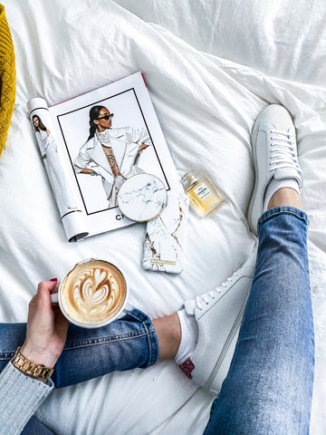Girl on bed with designer shoes, Chanel perfume, capuccino and magazine