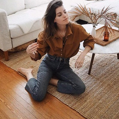 Woman Wearing Tan and Denim Capsule Outfit in Minimalist Setting