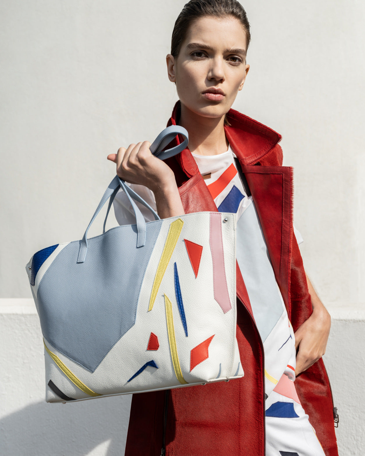 Akris colorful cut-out patchwork bag held by woman