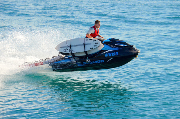 Jet ski getting air with surfboards secured in racks