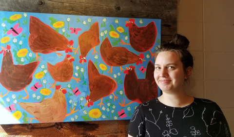 """Jess standing in front of her 2 x 3 foot painting """"The Chickens are Out!"""" in her local art gallery."""
