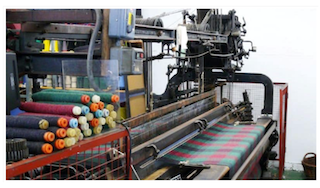 A machine that manufactures rugs of many sizes and makes is showcased.