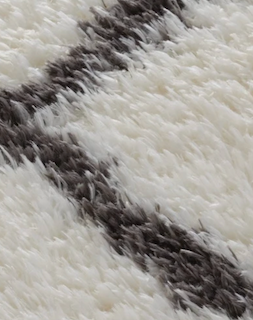 A closeup is taken of a shag rug, to showcase how long each fiber/yarn on the rug actually extends.