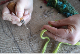 A hand-hook is being showcased as a way of explaining what the process of making a hand-hooked rug looks like.