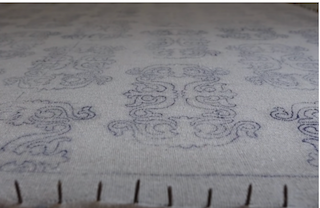 A canvas-like backing, with a printed pattern to guide the tufting process of the rug.