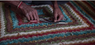 A surface layer of the rug is being sheared by a worker, with a pair of scissors.
