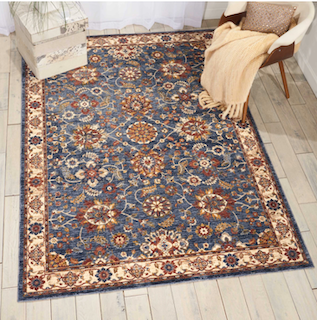 A traditional periodic pattern style rug, with a blue and beige color theme is displayed in a personal space setting.