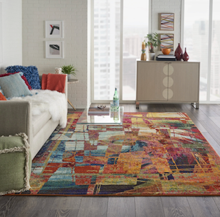 A vibrant, colorful contemporary style 8x11 rug is displayed in a living room space.