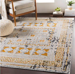 A 5x8 orange and cream transitional rug is placed in a living room setting, with a chair  on top of it.
