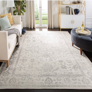An 8x11 grey and beige vintage style rug sits underneath furniture in a living room.