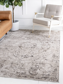 A beautiful 5x8 grey and beige, vintage style rug brings cohesion to a living room.